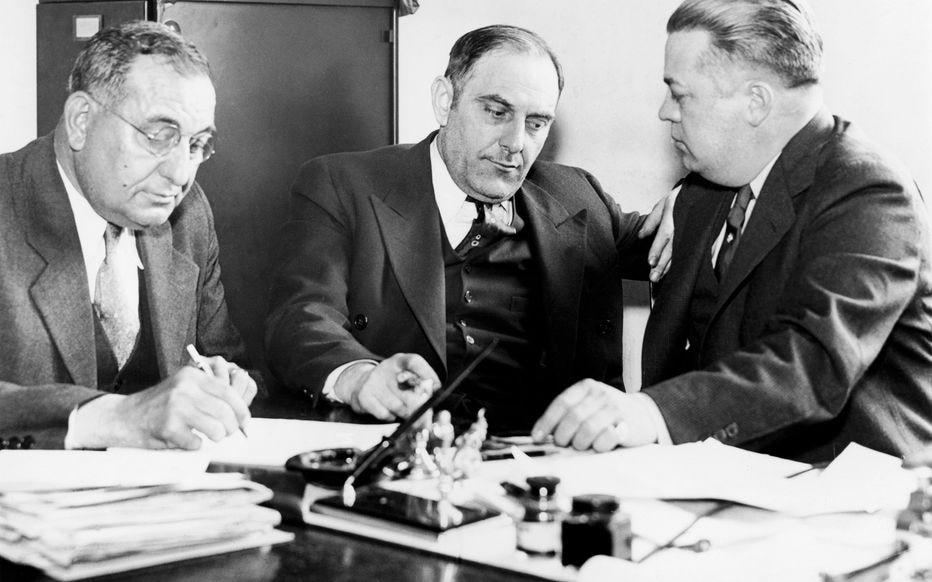 Interrogatoire de Victor Lustig (au centre) en 1935 par des agents de police américains